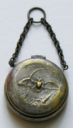 Victorian Bat and Quarter Moon Chatelaine Piece, it features a bat flying over a town with a quarter moon in the background. The chatelaine piece could have functioned to hold rouge or coins.