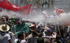 Manifestantes enfrentam a polícia durante protesto contra a visita de Barack Obama em Manila, nas Filipinas. Foto: Bullit Marquez/Associated Press