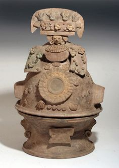 "Superb / Complete Mayan Incensario. Pre-Columbian, Maya Territories, Esquintla, Guatemala., ca. 550 -950 CE. Terracotta vessel with original pigments. Complete incensario (extremely rare to have top and bottom still together), depicting a Teotihuacan-style mask with a huge headdress and large earspools, spondylus shells in relief; bottom depicts a stylized face with two ears and ear ornaments and a Teotihuacan-style nose ornament. Massive size - 20""H x 12""W"
