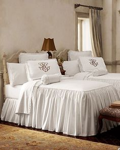 Twin skirted bedspreads with monogramed box shams. Top of bedspread has filler.