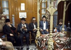 Photograph of Jewish men reading Hebrew prayers and celebrating Havdalah ritual in a private synagogue in Fez (Fes), Morocco. The Havdalah service marks the end of the Shabbat (Shabbos) holiday in the Jewish religion. The service includes lighting a candle. The small synagogue is attached to a private home of a Moroccoan Jew. Photograph by Nathan Benn taken February 16, 1980.