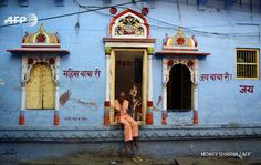 INDIA, Jodhpur : An Indian man sits in a doorway of a temple in Jodhpur on August 24, 2015. AFP PHOTO / MONEY SHARMA