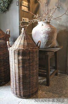 Seizoen en Stijl. Brass hardware on lidded basket. Terra cotta pot highly textured. Grey wall paint.