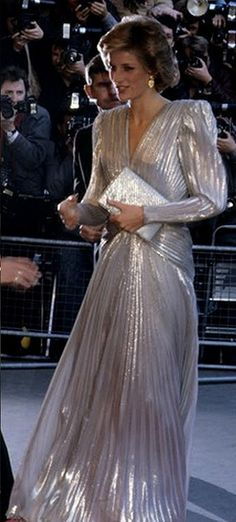 "Silver, shimmering gown with an exposed back designed by Bruce Oldfield. Diana wore this gown in March 1985 for a fashion show gala to aid Dr. Barnado's Charity, which she was president of. Because of the wide shoulders of this gown and a few others, Diana soon received the nickname ""Dynasty Di."""