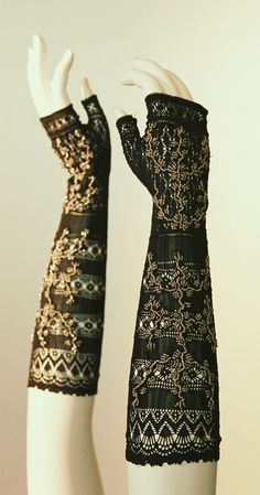 """Mitts: ca. 1830's, lacy silk knit with embroidery of metal beads. """"These mitts, reaching to just below the bend of the elbow, have a geometric knit pattern and they are decorated with shiny beads. Because they allow fingers to be freely moved, mitts are more functional than gloves. They became popular in the late 18th century. Some fashion plates of the period depict women embroidering or reading when wearing such mitts."""""""