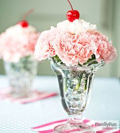 """Making these carnation """"sundaes"""" is a great pre-party activity for the kids. Have them place glass marbles in each dish, leaving an inch or so of space at the top, then add water. Insert the carnations and top with a cherry.                  Originally published in the May 2015 issue of FamilyFun magazine."""