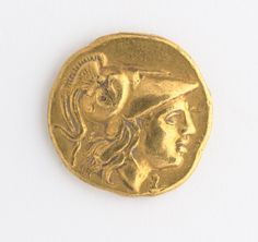 Greek, Macedon   (4th century B.C.) Stater  336–323 B.C.  gold. side A: Head of Athena wearing necklace, earring, and Corinthian helmet side B: Nike holding a wreath and naval standard