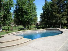 Beautiful free form pool with raised spa and water features. Wet Edge Satin Surface