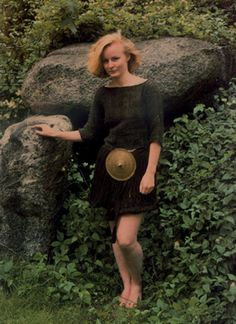 A woman wearing clothing in the style of the early bronze age (ca. 1400 BC) and standing at the entrance of a typical Danish dolmen. Photograph copyright by the National Museum of Denmark.