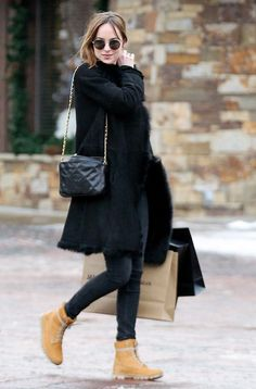 Dakota Johnson wears a black coat, fur stole, Chanel bag, skinny jeans, Timberland boots, and round sunglasses