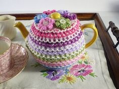 The coloured stripes on this tea cosy are worked in a thick, slip stitch pattern which will help to keep the tea hot. Only small amounts of each colour are needed and the cosy is topped with little knitted flowers to match the stripes.