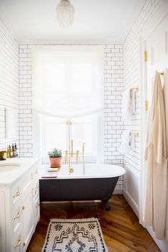 Serene bathroom with white subway tiles, chevron flooring, and brass hardware
