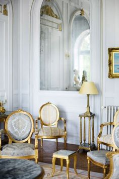 french living room. White walls and panelling trim, gold gilt chairs, beautiful