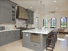 example of light countertops, cabinets, and travertine floors