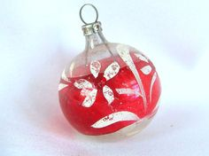 This vintage Christmas ornament is a small, round silver ball with a wide red stripe around the center. There is a hand painted spray of white flowers