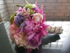 Light Pink Peonies, Pink, Lavender and Ivory Garden Roses, Lisianthus, Caspia, Limonium, Astilbe, Lilac and Pink German Statice and Antique Hydrangea hand-tied in ivory and taupe rosette taffeta.