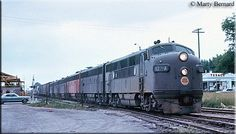 A parade of Chicago Great Western covered wagons led by F3A #107-A pull their freight train through Elmhurst, Illinois on June 26, 1966.