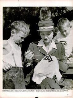 Mrs. Bob Hope repairs damage to youngster's torn shirt. She and her husband, the famous entertainer, were at the opening of a YMCA camp for war workers's sons. Appeared Dec. 20, 1943 in LIFE magazine ~