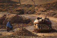 Photos of Life in Afghanistan. This is an image of A man and woman riding past an old destroyed Russian tank at Sarkhom Manda, Tarin Kowt District, Oruzgan Province.  This reminds me of the part of Boy Overboard when they are playing soccer.