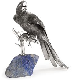 AN ITALIAN SILVER LARGE PARROT ON LAPIS BASE, GIANMARIA BUCCELLATI, MID-20TH CENTURY realistically modeled bird with textured body and chased overlapping feathers, perched on branch slottinmg into a boulder of lapis lazuli tailfeather marked GIANMARIA BUCCELLATI 925