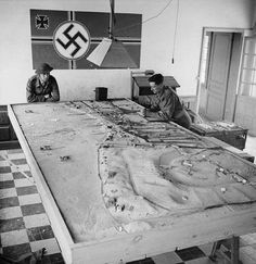 Canadian soldiers studying a German plan of the beach during D-Day landing operations. Photographer: Ken Bell