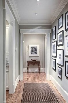 Gorgeous hallway with grey walls, wooden floors and black framed photos on the wall