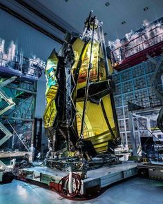 JWST: Ghosts and Mirrors - Ghosts aren't actually hovering over the James Webb Space Telescope. But the lights are out as it stands with gold tinted mirror segments and support structures folded in Goddard Space Flight Center's Spacecraft Systems Development and Integration Facility clean room. Following vibration and acoustic testing bright flashlights and ultraviolet lights are played over the stationary telescope looking for contamination easier to spot in a darkened room. In the dimness…