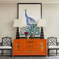 Jonathan Adler A pair of Chinese Chippendale chairs, an orange credenza, a peacock print, and a pair of pagoda lamps combine in this chic vignette.
