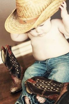 Cute picture of a country baby putting on his boots and cowboy hat gear n up