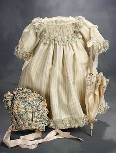 """""""What Finespun Threads"""" - Antique Doll Costumes, 1840-1925 - March 12, 2017: 307 Delicate Flannel Dress with Smocked Yoke, Ruffled Silk Bonnet, and Silk Parasol"""