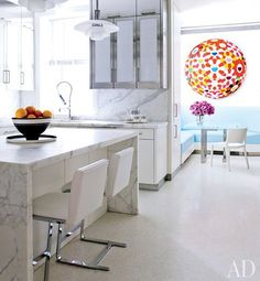 A colorful work by Takashi Murakami brightens the breakfast area of the kitchen, which has stainless-steel-and-milk-glass cabinetry and Calacatta gold marble counters and backsplashes | archdigest.com