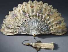 1858   Queen Victoria's Birthday Fan. Painted cream silk and pierced mother-of-pearl, includes emblems of the British Isles, rose (England), shamrock (Ireland) and thistle (Scotland) and Queen Victoria's 'VR' monogram surmounted by a crown, lilies-of-the-valley, the birth flower for the month of May, and the Queen's cipher ('VR' and 'A') and crown and the date 24 May 1858, her thirty-ninth birthday. (Royal Collection/© Her Majesty Queen Elizabeth II 2015) royalcollection.org.uk