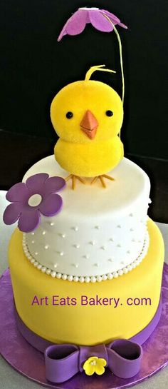 Two tier white, #yellow and #purple #baby #shower #cake design with edible bow,  flowers and pearls. The baby chick topper is not edible.