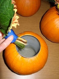 Carve out a place for a can in a pumpkin.  Fill with water and put flowers in it.