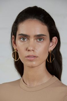 Movil earrings by Luz Ortiz. Influenced by post modern and Bauhaus, the Movil earring features two hinged semicircles allowing mobile movement throughout the design. Wear open, sideways or closed these earrings are versatile and timeless. Handcrafted in 18k gold plated brass.