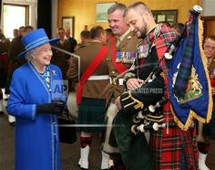 The queen talking to major richard grisdale pipe major of the royal regiment of scotland after having presented the regiment with a new pipe banner