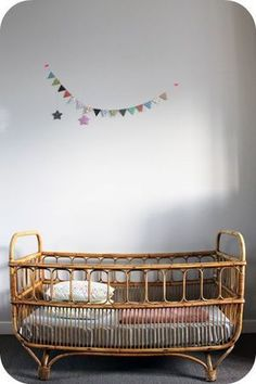 crib. Cute wooden cot in a simple room. Quite retro with rattan features