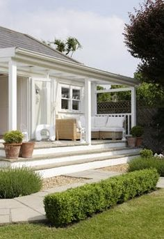 I do love a white porch  simple  classic  summer: note wrap around low rise, wide steps, note petite hedge
