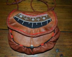 This bag is made of two different reindeer leather with willow and birch bark. The leather is naturally hand tanned and bag is also hand stitched. The pattern is traditional saami styly, but the decoration with kauri shells and fish bones is my own. I have stiched a mandala model and the bones, shells and small stones are symbolising the family members. The diameter of bag is app. 27 cm height 24 width max 26cm on mouth width 18 cm The cord length: 120cm There is lining inside the bag…