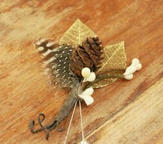 A rustic-style boutonniere featuring a mini pinecone, gold skeleton leaves, feathers, and faux berry accents.  Lovely for a rustic or woodland wedding...