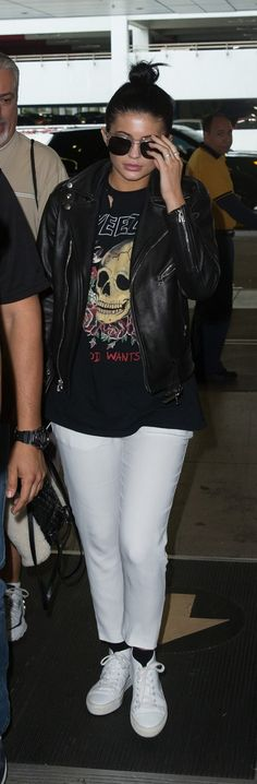 Kylie Jenner wears a graphic t-shirt, leather moto jacket, cropped white pants, and high-top sneakers