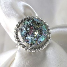 Vintage ring! Gorgeous vintage Sarah Coventry ring. Part of the Northern Lights collection. Silver tone with an amazing iridescent design! Shades of hematite, teal, violet, indigo. Its really quite a stunner. Band is a bit bent but doesn't affect wear or comfort. Size 8. Sarah Coventry Jewelry Rings
