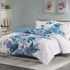 "Introduce a fresh splash of color to your bedroom with this comforter set. The ultra-soft comforter pops with an asymmetrical floral in shades of blue that is printed against a gray Ogee ground. A solid blue reverse adds more color to the bedding set, while coordinating sham(s) harmonize with the top of the bed. An embroidered square pillow with the typographical phrase ""less Monday more weekend"" and an oblong pillow with fabric manipulation provide the finishing touches to the ensemble…"