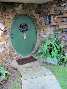 "green door on a stone hobbit house - ""adults are allowed inside only in the company of children"""