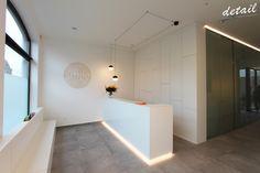 Eenvoudige witte balie met speelse accenten , zoals de verlichting (Flos lighting) en wanddecoratie.