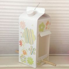 Milk carton bird feeder: spray paint, die-cut paper, mod podge, wooden dowel (could just use a branch), paper clip.