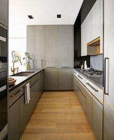 The modern and masculine galley kitchen opens up to the rest of the light-filled apartment   archdigest.com