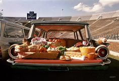 "Fall 1960 Arthur Rothstein, for Look magazine. ""Food for tailgate picnics displayed in the backs of station wagons, including a Ford Country Squire, a Dodge Lancer, and a Pontiac Bonneville Safari parked in a football stadium."""