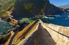 """SAN JUAN DE GATZELUGATXE """"Castle rock"""" in Basque, visitors reach Gaztelugatxe's rocky island outcropping by a stone bridge that looks like a transplanted piece of the Great Wall of China leading to the 10th-century hermitage of St. John the Baptist. The trail to the bridge is a wild footpath that descends through pine forest and ferns."""