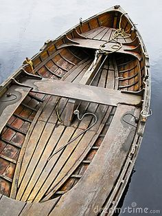 Old wooden rowboat floating on placid water